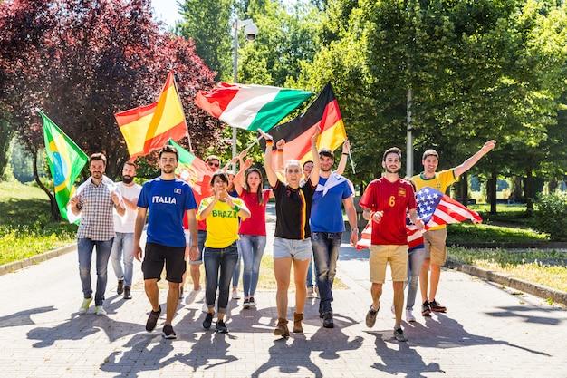 Glückliche fans anhänger aus verschiedenen ländern gehen und singen zusammen