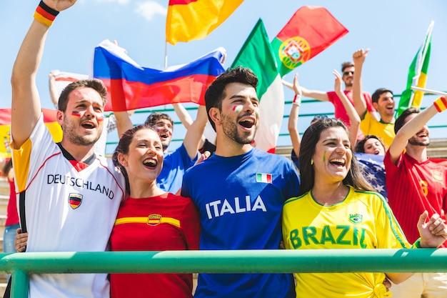 Glückliche fans fans aus verschiedenen ländern zusammen im stadion