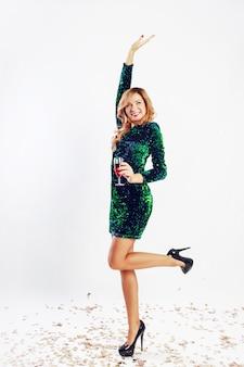 Glückliche feierfrau im grünen paillettenkleid, das wein trinkt und party genießt. goldenes konfetti.