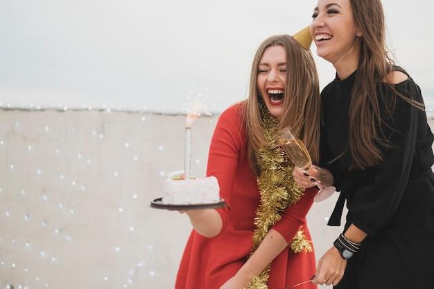 Glückliche feiernde mädchen auf der dachspitzenparty