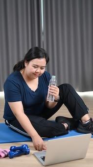 Glückliche fettleibige frau, die eine wasserflasche hält und zu hause fitnesstrainingsvideos auf dem laptop ansieht.