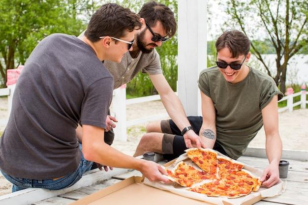 Glückliche firma mit der pizza, die in der natur stillsteht