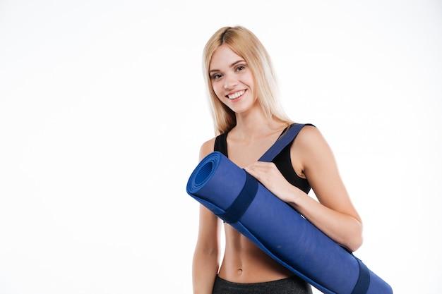 Glückliche fitness-dame, die sportteppich hält