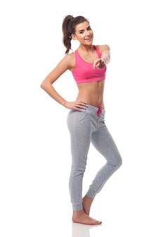 Glückliche fitnessfrau, die an der kameraseite zeigt