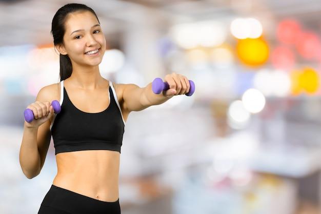 Glückliche fitnessfrau, die hanteln hebt