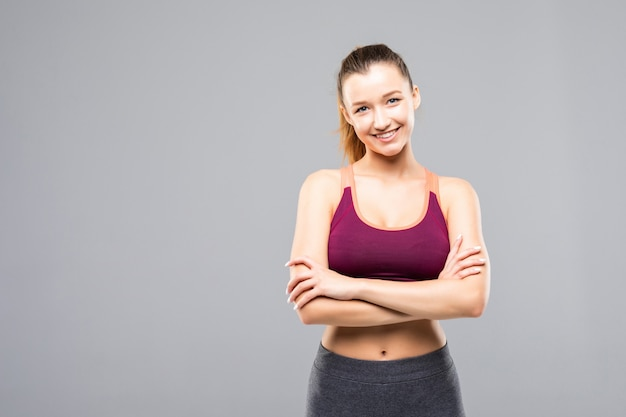 Glückliche fitnessfrau, die mit verschränkten armen steht