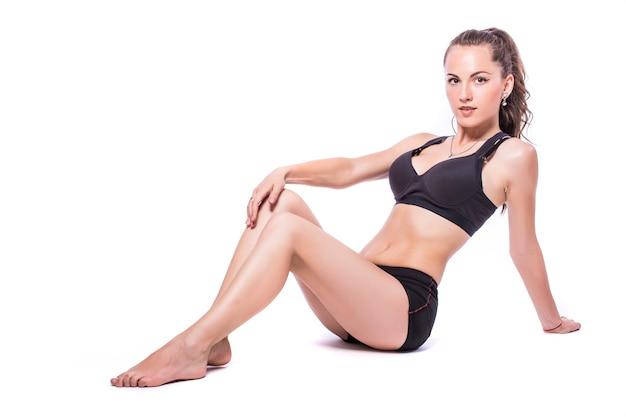 Glückliche fitnessfrau, die streckübungen lokalisiert auf einem weißen hintergrund tut.