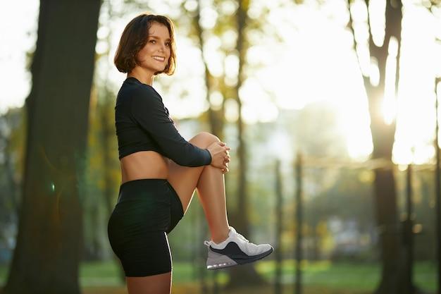Glückliche fitnessfrau, die während des sonnigen tages im park steht