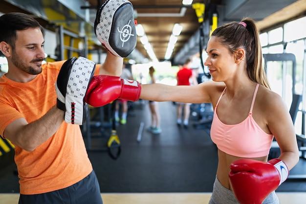 Glückliche fitte frau übungsboxen mit personal trainer im fitnessstudio. sport, gesundheit, menschenkonzept