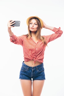 Glückliche flirtende junge frau, die bilder von sich durch handy, über weißem hintergrund macht