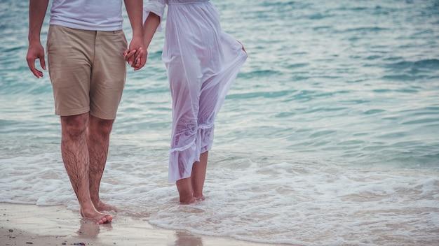 Glückliche flitterwochen der paare romantisch in der liebe am strandsonnenuntergang. verliebt am strand.