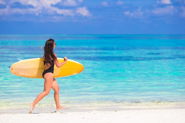 Glückliche formschöne brandungsfrau am weißen strand mit gelbem surfbrett