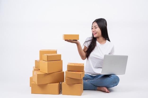 Glückliche frau an der hand befindet sich eine paketbox. weißer hintergrund online-shopping-betreiber