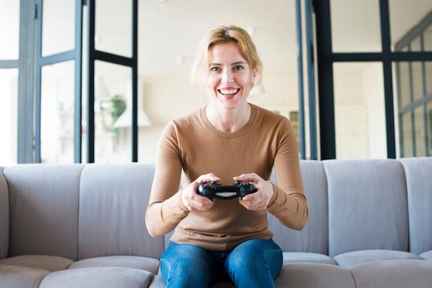 Glückliche frau auf der couch, die spielkonsole spielt