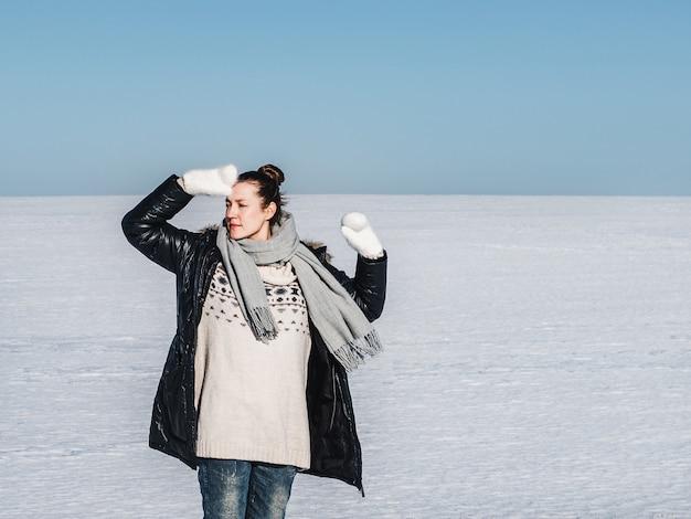 Glückliche frau auf einem hintergrund eines schneebedeckten feldes