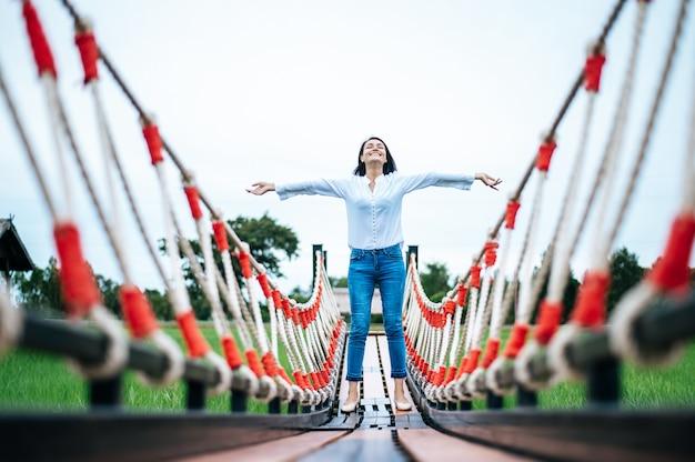 Glückliche frau auf einer holzbrücke in einer grünen wiese an einem sonnigen tag