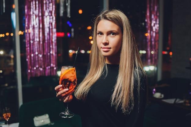 Glückliche frau auf einer party, die lächelt und einen cocktail trinkt.