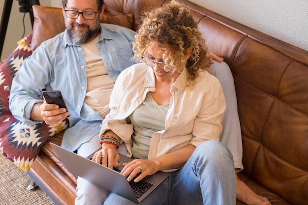 Glückliche frau benutzt laptop, der zu hause mit ihrem mannmann auf dem sofa sitzt, der telefon benutzt