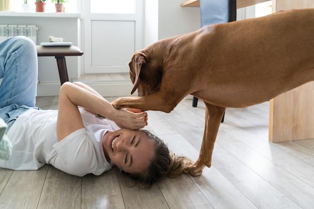 Glückliche frau besitzerin spielt mit ihrem schönen vizsla hund, umarmt, küsst, liegt zu hause auf dem boden