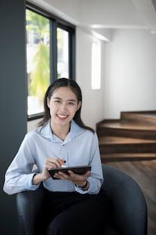 Glückliche frau büroangestellte, die digitale tablette hält und in die kamera lächelt, während sie im büro sitzt.