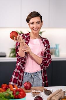 Glückliche frau des apfels in der hand wählen früchte aus, die in der küche kochen. hausfrau kocht apfelkuchen, der an der küche steht und kariertes hemd mit einem kurzen haar trägt