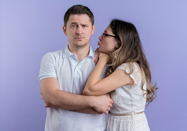Glückliche frau des jungen paares, die ihren geliebten mann betrachtet, der über blau küssen wird