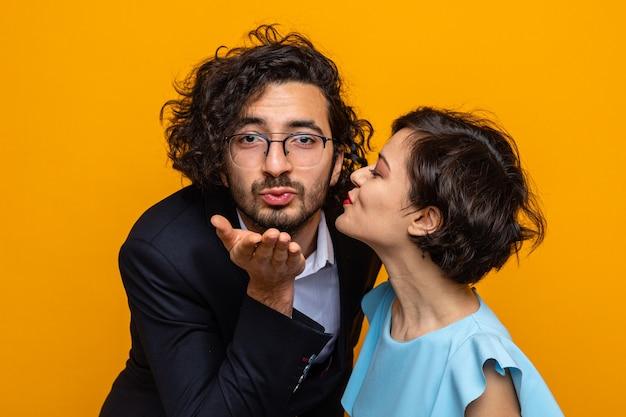 Glückliche frau des jungen schönen paares, die ihr lächeln küsst, das einen kussfreund bläst, der den internationalen frauentag 8. märz feiert, der über orange hintergrund steht