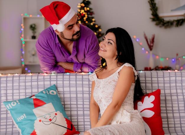 Glückliche frau des jungen und schönen paares, die auf einer couch sitzt, während ihr freund in der weihnachtsmütze, die hinten im geschmückten raum mit weihnachtsbaum im hintergrund steht