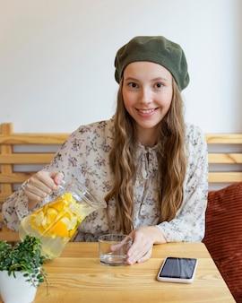 Glückliche frau des mittleren schusses, die am tisch sitzt und limonade gießt
