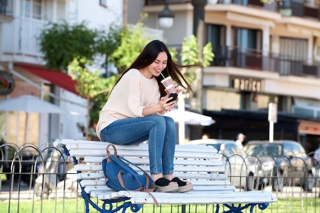 Glückliche frau des vollen körpers, die auf bank mit telefon und getränk sitzt