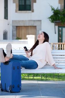 Glückliche frau des vollen körpers mit koffer und mobiltelefon auf parkbank