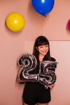 Glückliche frau, die 25 foliengeburtstagsballon hält