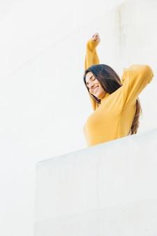 Glückliche frau, die am balkon ausdehnt