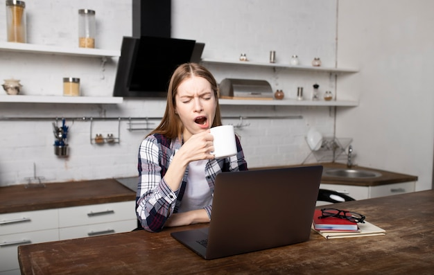 Glückliche frau, die am morgen zu hause arbeitet. junges mädchen gähnt. sie benutzt ihren laptop
