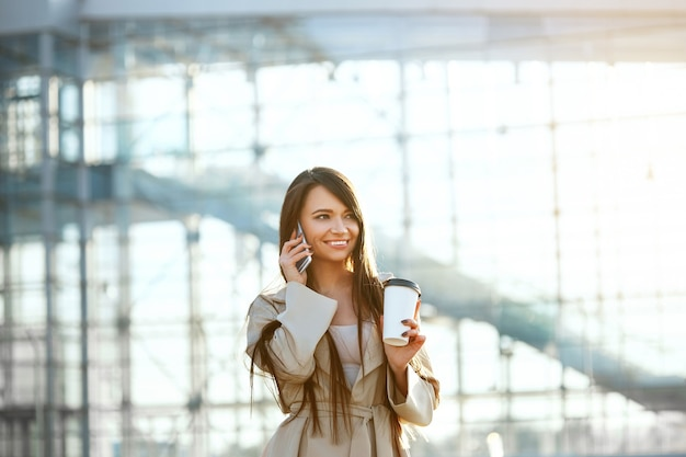 Glückliche frau, die am telefon anruft, das nahe büro steht. porträt der schönen lächelnden frau, die tasse kaffee in der hand hält und am telefon im freien spricht.