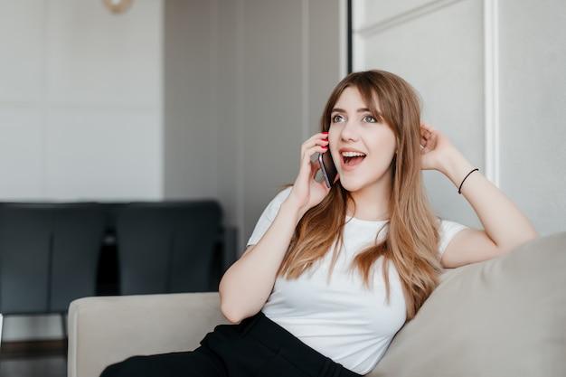 Glückliche frau, die am telefon spricht, das im wohnzimmer auf einer couch zu hause sitzt