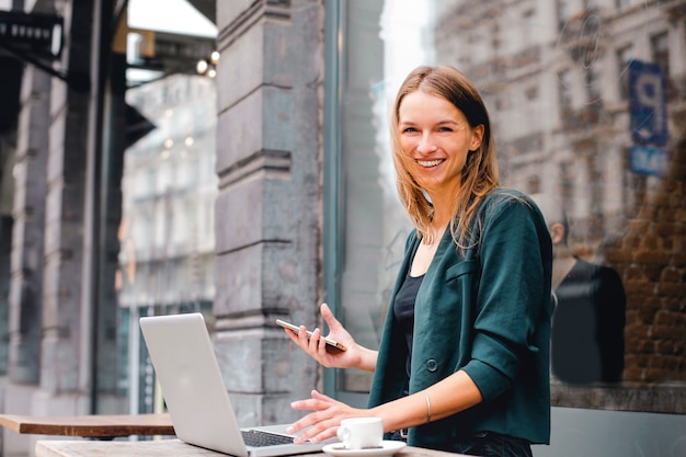 Glückliche frau, die an einem laptop im freien arbeitet