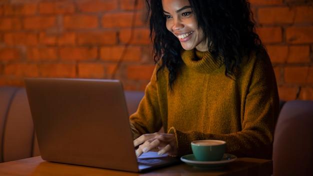 Glückliche frau, die an ihrem laptop in einem café arbeitet
