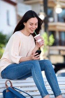 Glückliche frau, die auf bank mit mobiltelefon und getränk sitzt