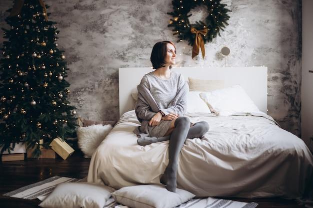 Glückliche frau, die auf bett nahe weihnachtsbaum sich entspannt