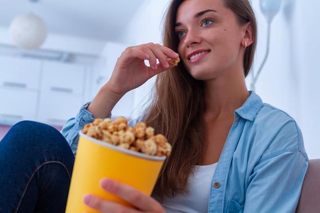 Glückliche frau, die auf couch stillsteht und zu hause knuspriges karamellpopcorn während des aufpassenden films isst