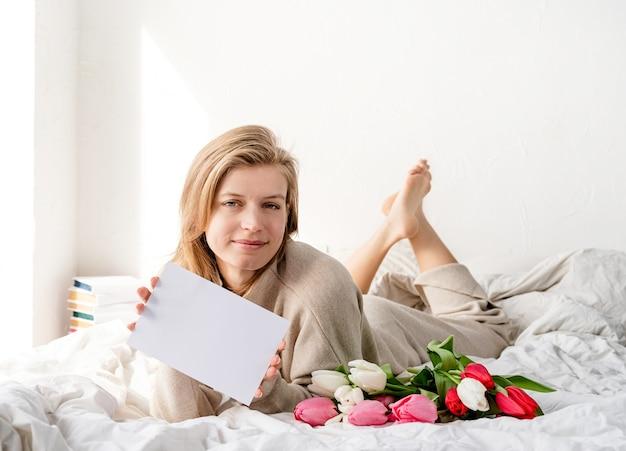 Glückliche frau, die auf dem bett liegt und pyjamas trägt und tulpenblumenstrauß und leere karte für modellentwurf hält