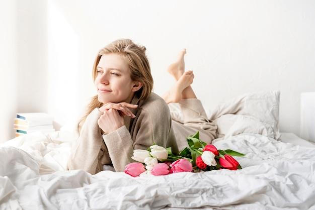 Glückliche frau, die auf dem bett liegt und pyjamas trägt und tulpenblumenstrauß und wein genießt