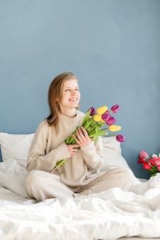 Glückliche frau, die auf dem bett sitzt pyjamas hält tulpenblumenstrauß, blauer wandhintergrund