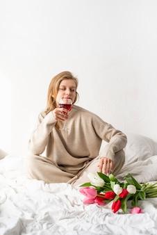 Glückliche frau, die auf dem bett sitzt pyjamas, mit vergnügen genießt blumen und ein glas rotwein