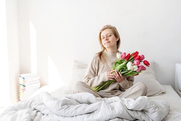 Glückliche frau, die auf dem bett sitzt und pyjamas mit geschlossenen augen trägt, mit vergnügen, blumen und romantisches geschenk am valentinstag genießend