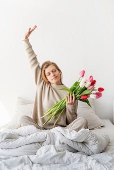 Glückliche frau, die auf dem bett sitzt und pyjamas trägt, mit vergnügen, blumen zu genießen und sich zu dehnen