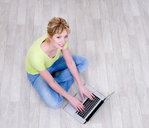 Glückliche frau, die auf dem boden mit laptop sitzt - hohe winkelansicht