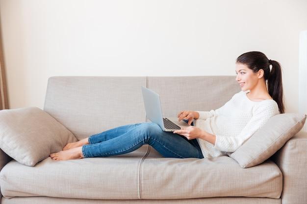 Glückliche frau, die auf dem sofa liegt und zu hause smartphone benutzt