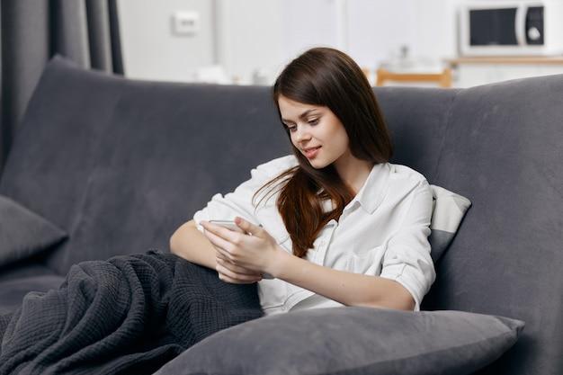 Glückliche frau, die auf der couch mit einem telefon in ihren händen innenkomfort sitzt